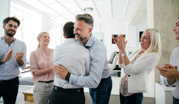 An office team are celebrating together, embracing and applauding each other after a successful business pitch.